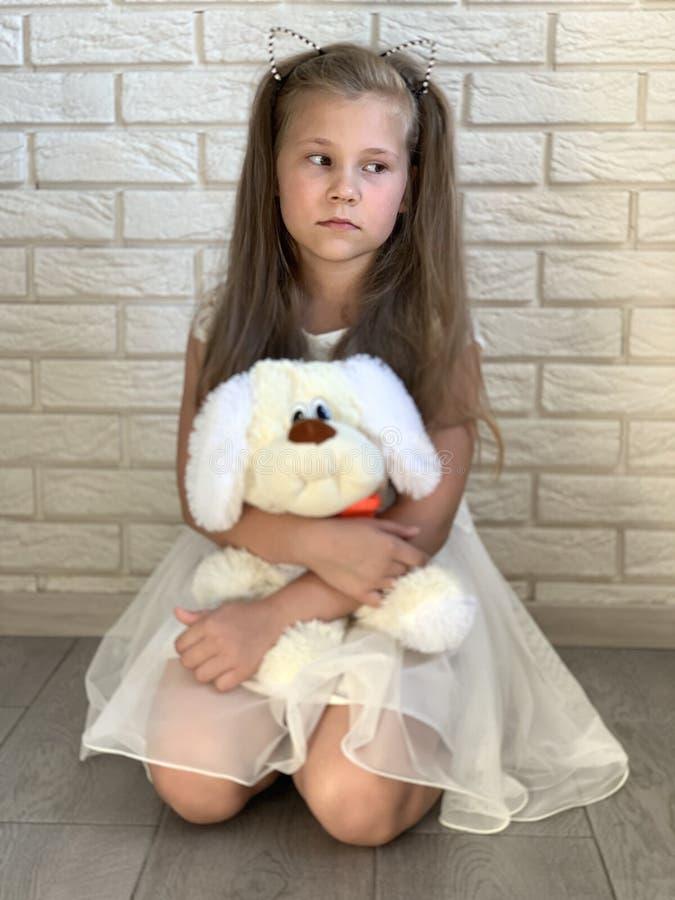 Lite flicka i en vit kl?nning En flicka med en toy arkivfoto