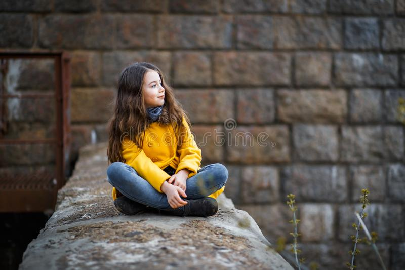 Lite flicka i ett gult lag under den järnväg järnbron på solnedgången royaltyfria foton