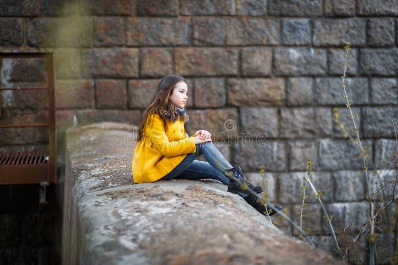 Lite flicka i ett gult lag under den järnväg järnbron på solnedgången royaltyfri foto