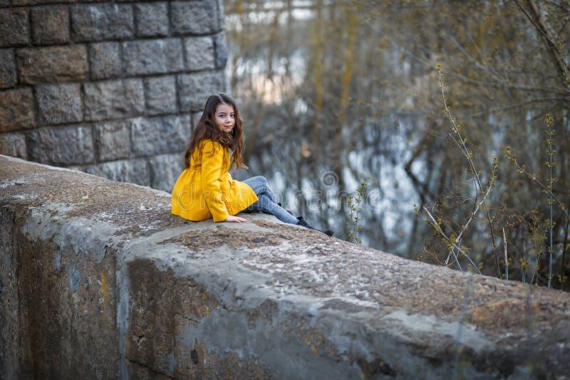 Lite flicka i ett gult lag under den järnväg järnbron på solnedgången royaltyfria bilder