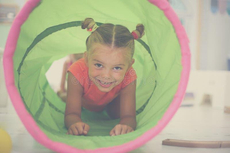 Lite flicka i lekplats Lilla flickan kör till och med tuen royaltyfria foton