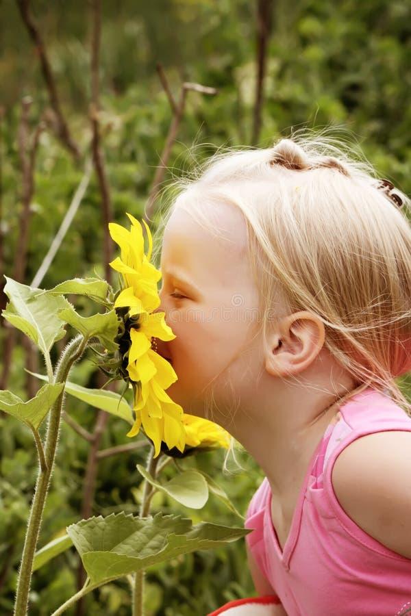 Lite flicka med blommor royaltyfria bilder