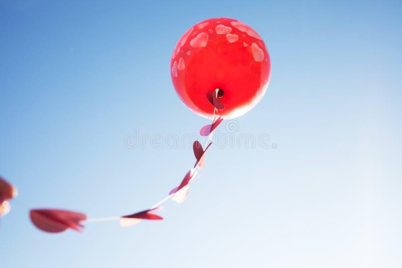 Lite flicka med den röda ballongen på den blåa himlen royaltyfria foton