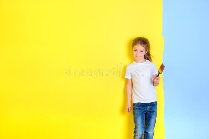 Lite flicka med en målarfärgborste i hennes händer royaltyfria bilder