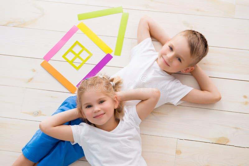 Lite flicka med en pojkelögn på golvet bredvid ett hus av kulört papper ovanför sikt royaltyfri bild