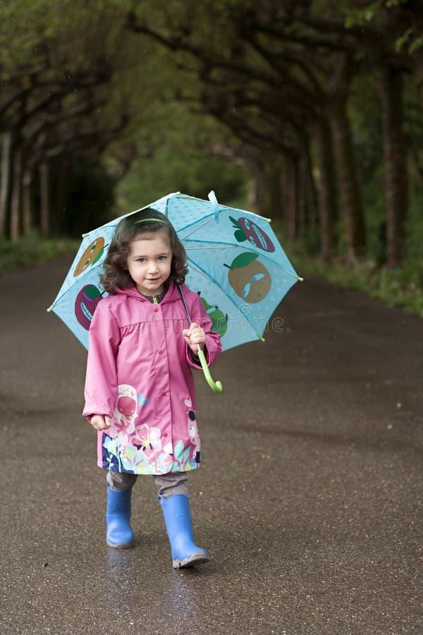 Lite flicka med ett blått paraply fotografering för bildbyråer