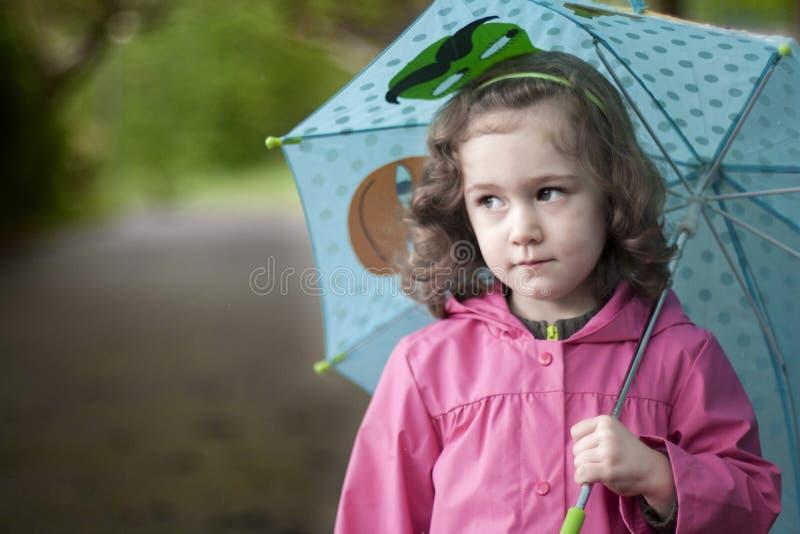 Lite flicka med ett uttråkat uttryck royaltyfri bild