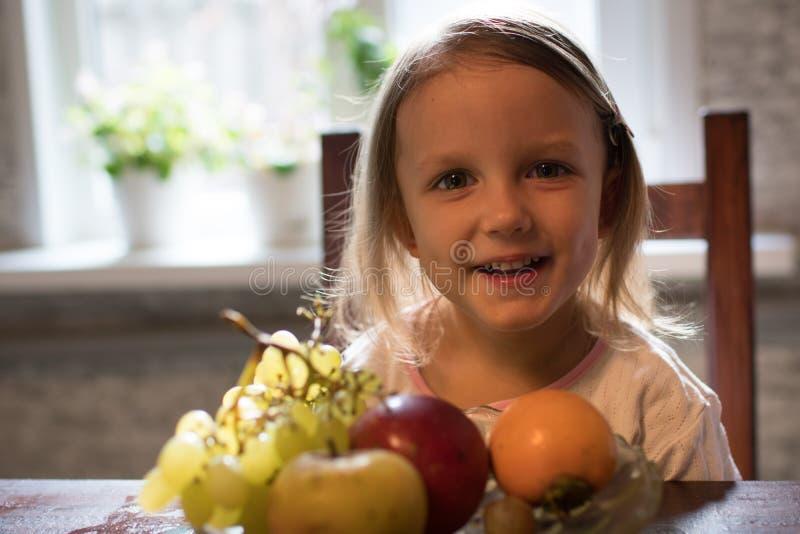 Lite flicka med frukt arkivbild