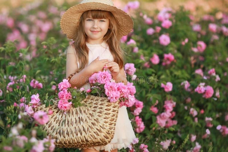 Lite flicka med h?rligt l?ngt blont h?r som ?r ikl?tt en ljus kl?nning och en krans av verkliga blommor p? hennes huvud, i royaltyfria foton