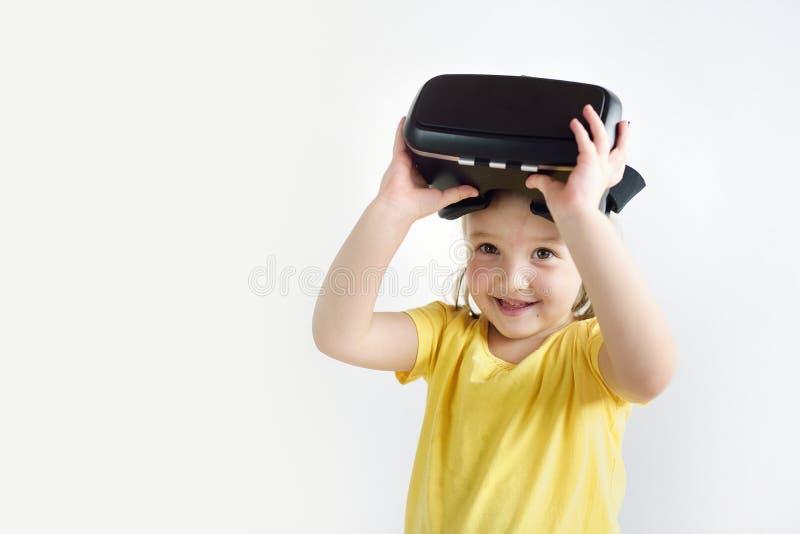 Lite flicka med virtuell verklighetexponeringsglas Skyddsglasögon för en virtuell verklighet för barn som bärande håller ögonen p royaltyfri foto