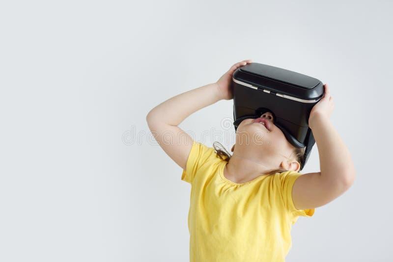 Lite flicka med virtuell verklighetexponeringsglas Skyddsglasögon för en virtuell verklighet för barn som bärande håller ögonen p royaltyfri bild