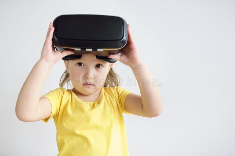 Lite flicka med virtuell verklighetexponeringsglas Skyddsglasögon för en virtuell verklighet för barn som bärande håller ögonen p royaltyfri fotografi