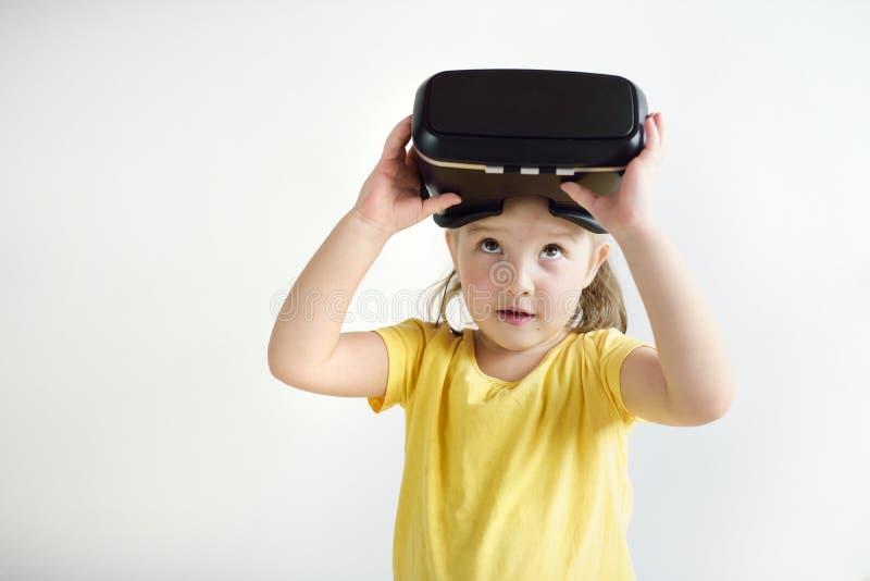 Lite flicka med virtuell verklighetexponeringsglas Skyddsglasögon för en virtuell verklighet för barn som bärande håller ögonen p royaltyfria foton