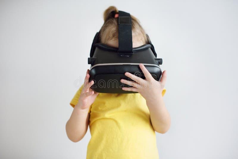 Lite flicka med virtuell verklighetexponeringsglas Skyddsglasögon för en virtuell verklighet för barn som bärande håller ögonen p arkivfoto