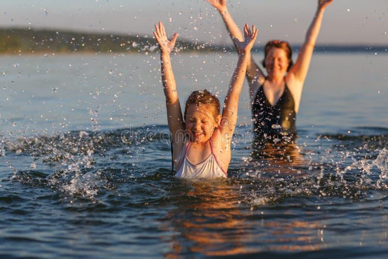 Lite flicka och hennes moder i vattnet av havet royaltyfri fotografi