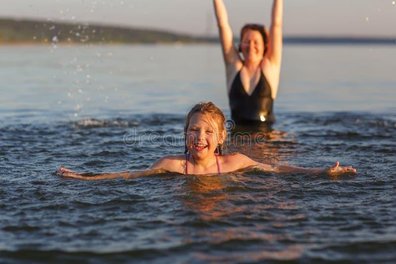 Lite flicka och hennes moder i vattnet av havet arkivbilder