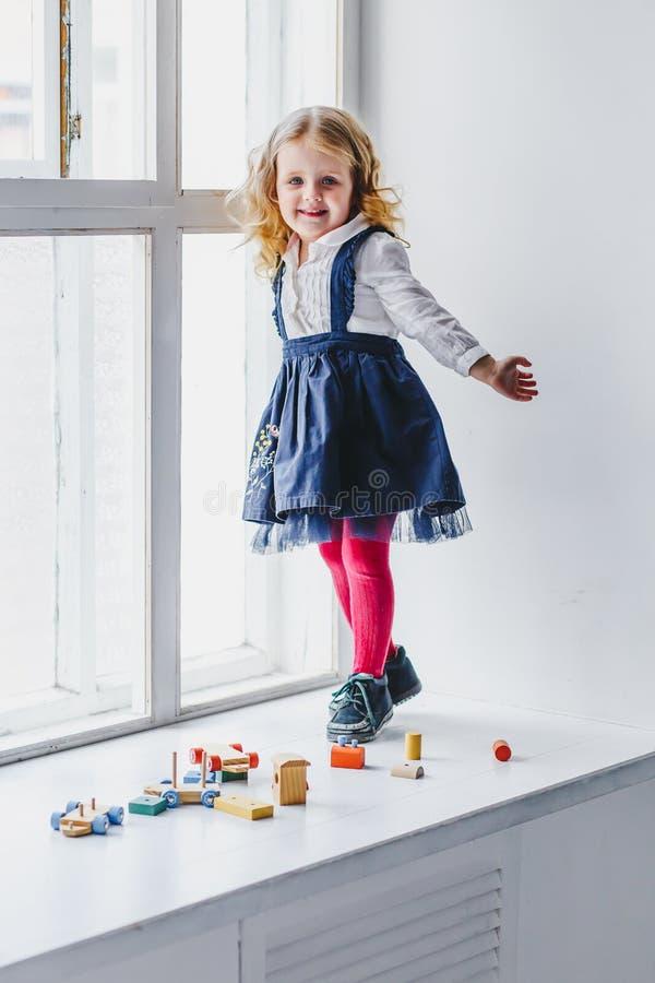 Lite flicka på fönsterbrädan i en klänning arkivfoto