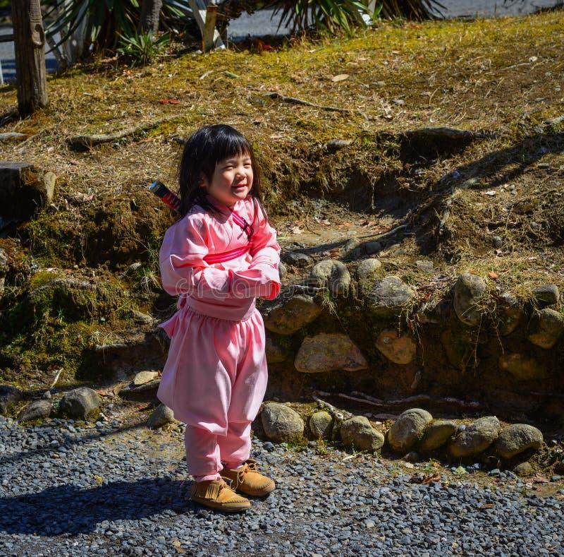 Lite flicka som bär den Ninja dräkten arkivfoton