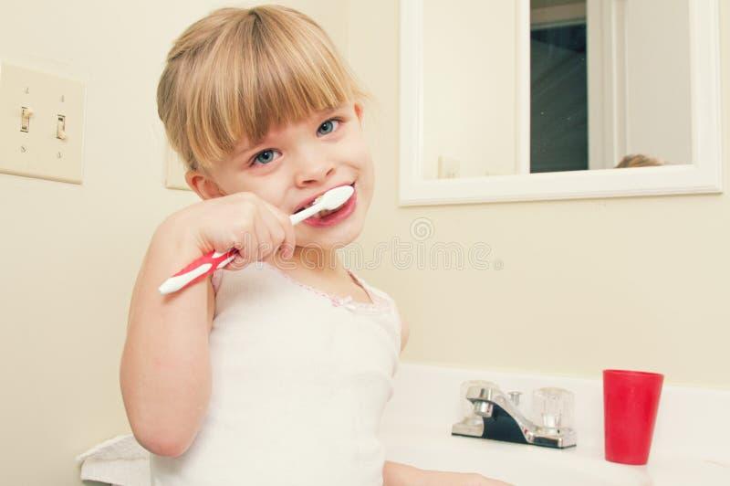 Lite flicka som borstar hennes tänder royaltyfria foton