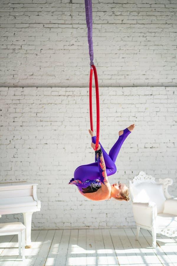 Lite flicka som kopplas in i flyg- gymnastik royaltyfri bild