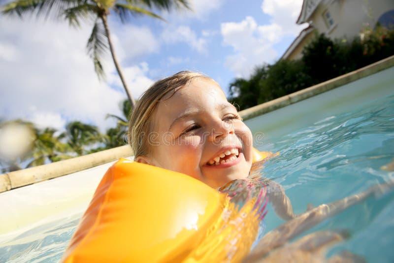Lite flicka som ler och simmar arkivfoto