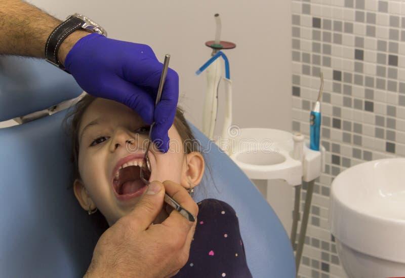 Lite flicka som sitter i en tand- stol på ett tand- kontor royaltyfri foto