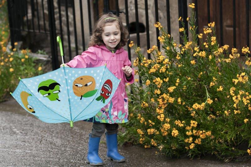 Lite flicka som spelar med ett färgrikt paraply arkivbilder