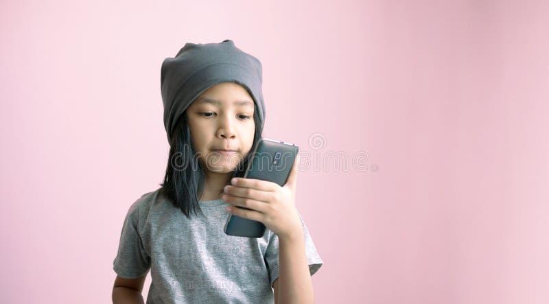 Lite flicka som spelar smartphoneselfie med lycka och att le Asiatisk flickainnehavtelefon med det gråa torkdukelocket på rosa fä royaltyfri fotografi