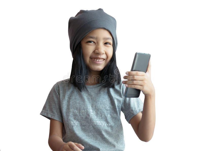 Lite flicka som spelar smartphoneselfie med lycka och att le Asiatisk flickainnehavtelefon med det gråa torkdukelocket på viten fotografering för bildbyråer