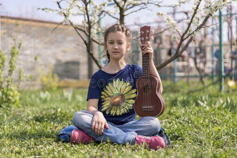 Lite flicka som spelar ukulelet i trädgården fotografering för bildbyråer