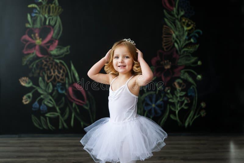 Lite flickadans i ett rum i en härlig klänning arkivfoto