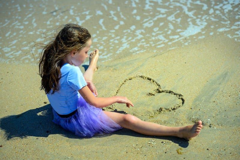 Lite flickasammanträde på den gula sanden på stranden i en purpurfärgad klänning och attraktioner en hjärta med hennes händer på  arkivfoton