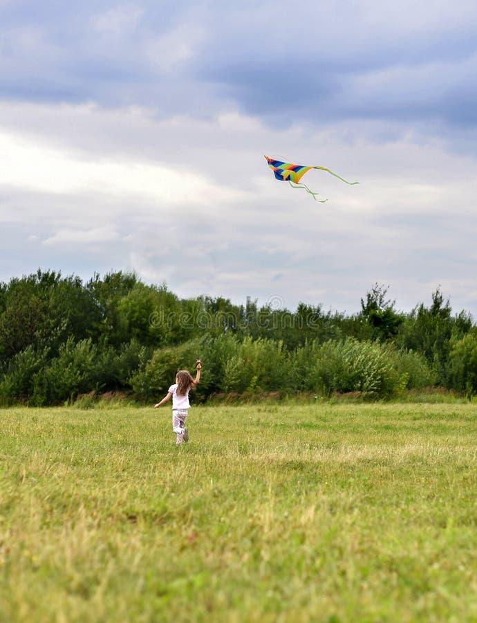 Lite flickaspring på grönt gräs efter den ljusa flygdraken arkivfoton
