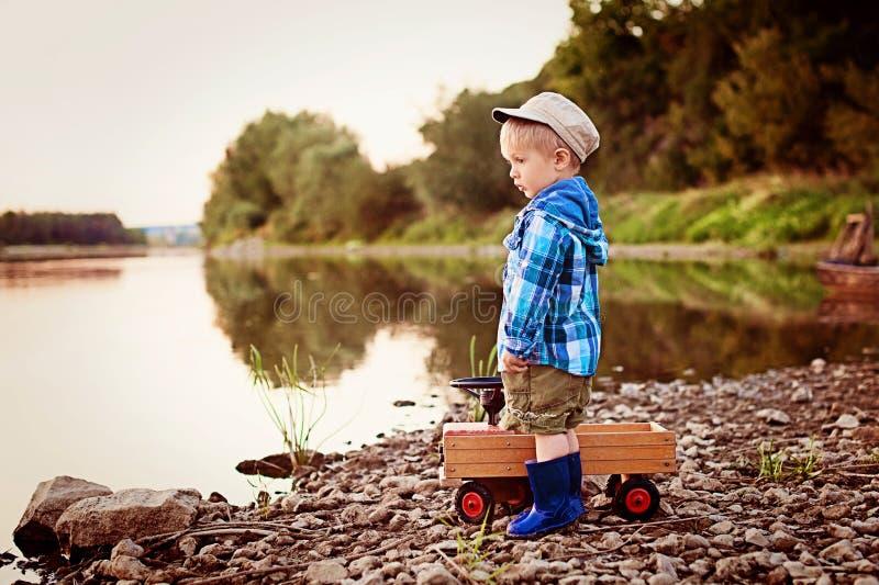 Lite fyra år gammal ledsen pojke som söker efter något på floden arkivbild