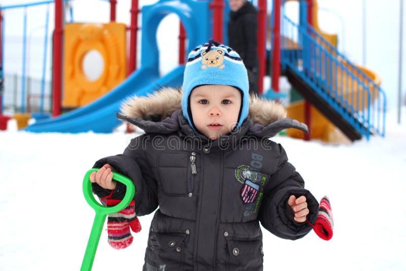 Lite går pojken i det insnöat vintern på bakgrunden av en lekplats royaltyfri foto