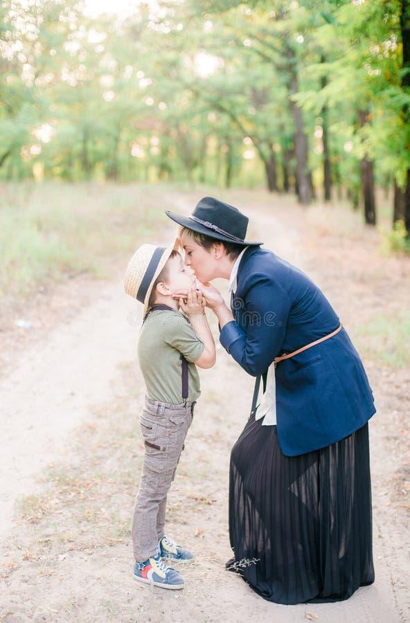 Lite går pojken och hans mamma i hattar in parkerar fotografering för bildbyråer