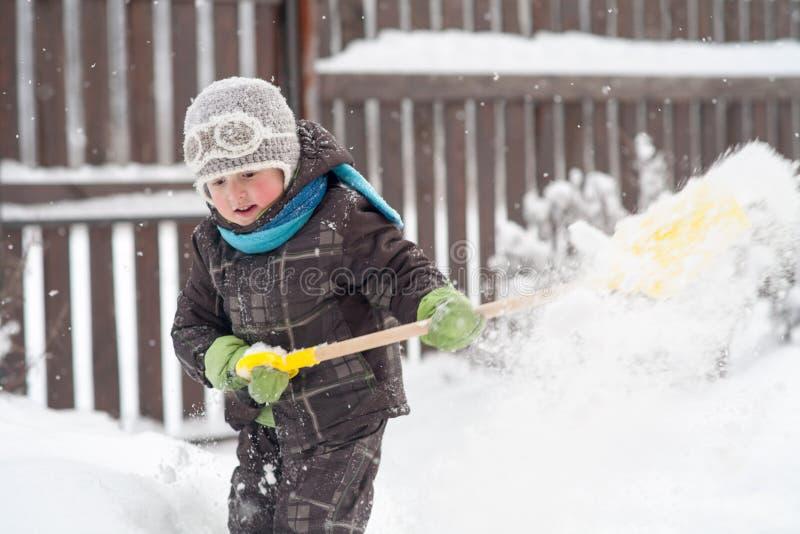 Lite g?r pojken ren banor f?r en skyffel i g?rden fr?n sn? arkivbild