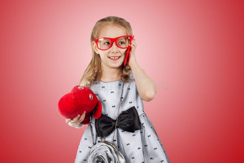Lite glamorös flicka med röda exponeringsglas, en hund och en ljus pho arkivfoto