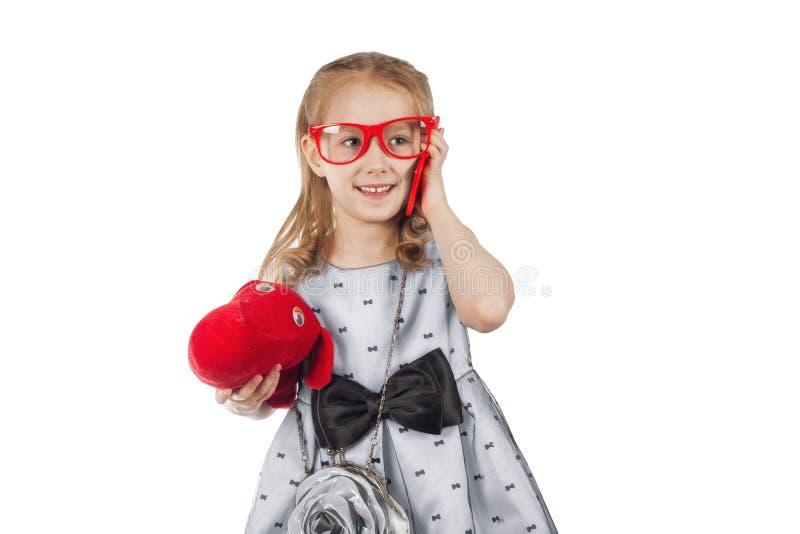 Lite glamorös flicka med röda exponeringsglas, en hund och en ljus pho royaltyfri foto