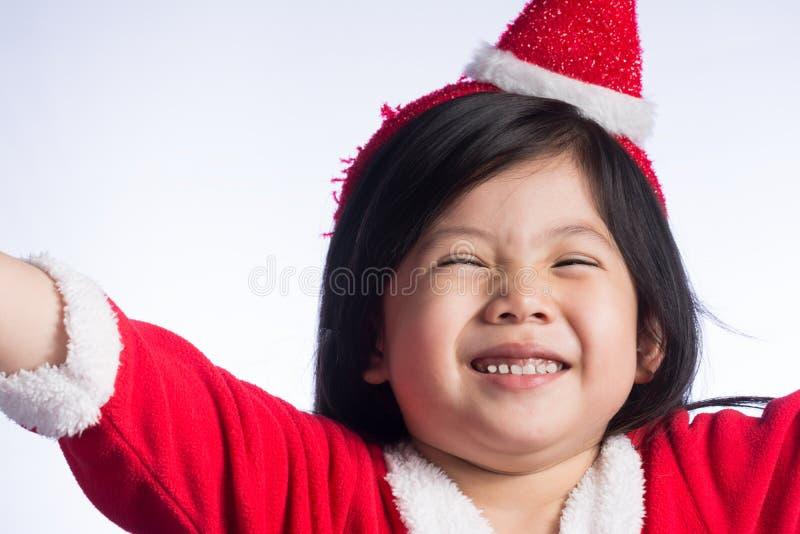 Lite gullig asiatisk flicka i den Santa Cross klänningen på vit backgroun royaltyfri foto