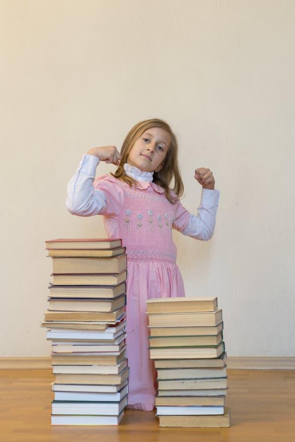 Lite gullig flicka i en rosa kl?nning som l?ser en bok som sitter p? golvet Begreppskunskap är makt royaltyfri illustrationer