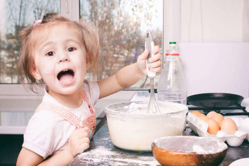 Lite gullig flicka som hemma f?rbereder degen i k?ket arkivbilder