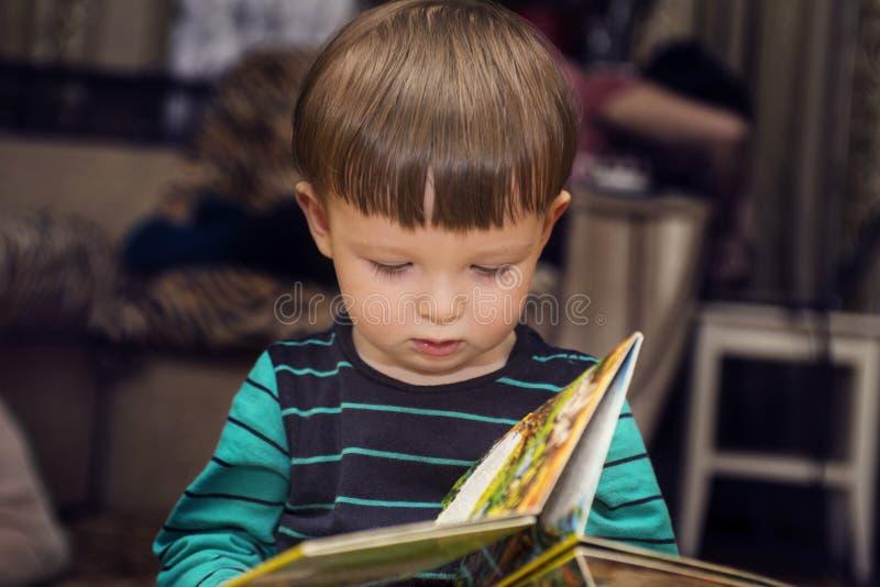 Lite gullig pojke som läser ett boksammanträde på golvet Hemmastadd barnläsebok fotografering för bildbyråer