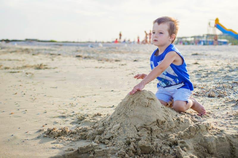 Lite gulligt behandla som ett barn pojken spelar på en strand nära ett hav Pojkebyggnadssandslott på stranden arkivfoton
