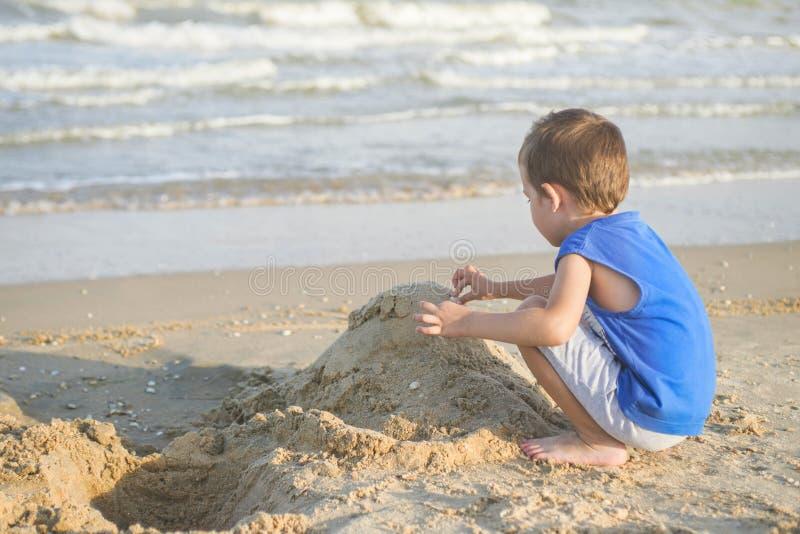 Lite gulligt behandla som ett barn pojken spelar på en strand nära ett hav Pojkebyggnadssandslott på stranden arkivfoto