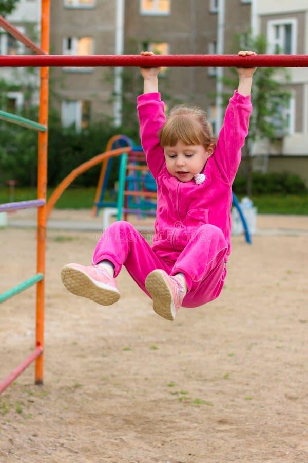 Lite hänger flickan på en stång och le Sund livsstil arkivbilder