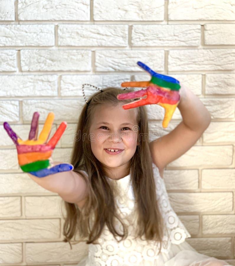 Lite har flickan gyckel, kulör målarfärg på hennes händer arkivfoton
