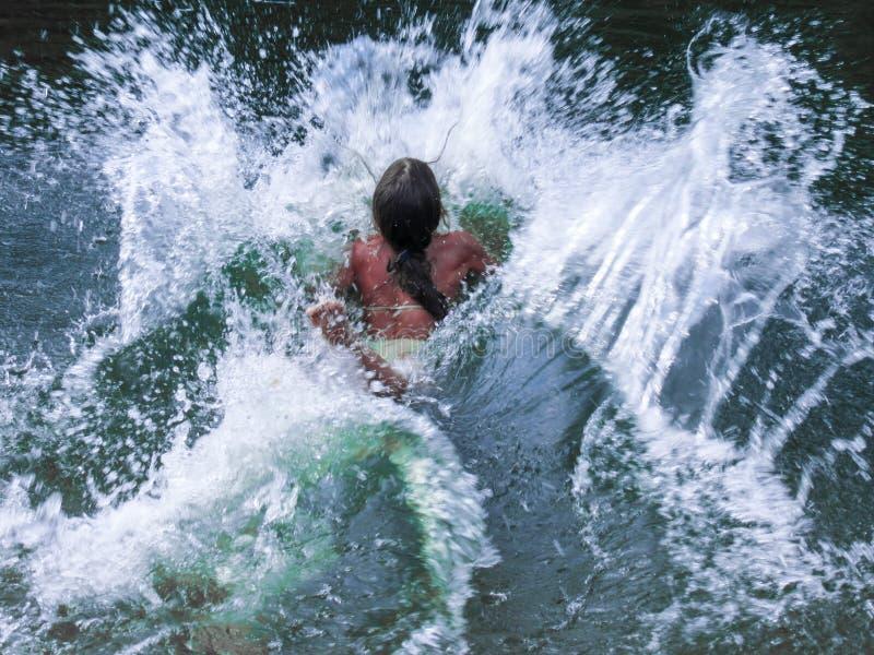 Lite hoppar flickan in i vattnet arkivfoton