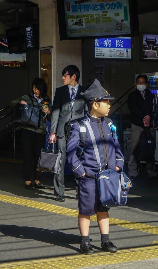 Lite japansk student att vänta på drevet royaltyfria foton