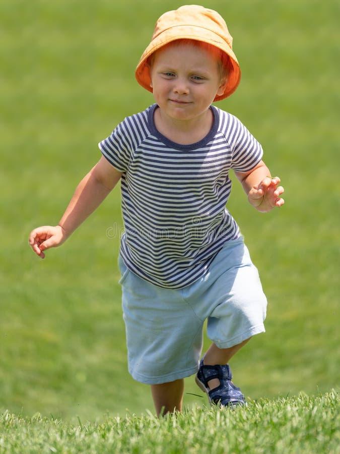 Lite kör pojken upp på den gröna kullen arkivbild